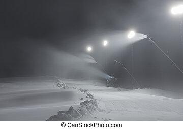 Ski slope with snow guns at night