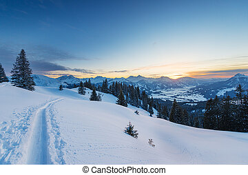 ski snow tracks in austrian mountains at winter sunset