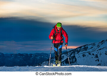 Ski touring at night in the last hours of the day
