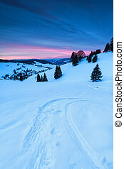 ski track on snow in mountains at sunrise