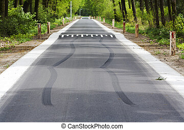 Skid marks in front of speed bump on a asphalt country road