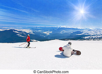 Skier and snowboarder skiing downhill in mountains, winter...