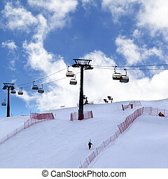 Skier ascend on snow ski slope and ski-lift at evening -...