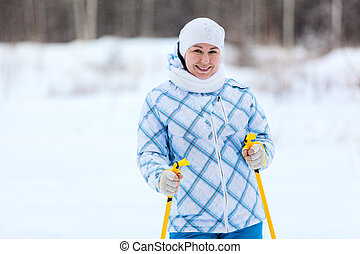 Skier Caucasian woman portrait with ski poles in hands