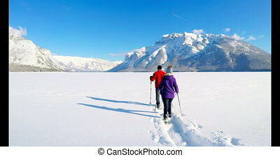 Skier couple walking on snowy landscape during winter 4k -...