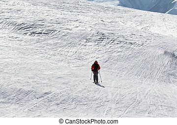 Skier downhill on snow off-piste slope in sun winter day....
