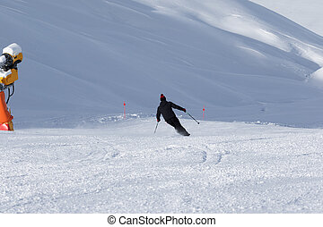 Skier downhill on snowy ski slope with snow cannon at sun...