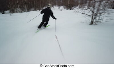 Skier enjoys idyllic perfect weather on winter day for recreation skiing down the fresh groomed piste. Tracking slow motion