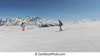 Skier going down the snowy slope, follow shot from the side