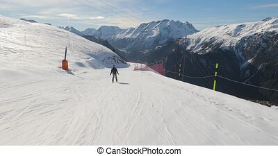 Skier going down the snowy slope, follow shot in 60 fps 4k