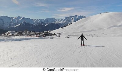 Skier going down the snowy slope, follow shot