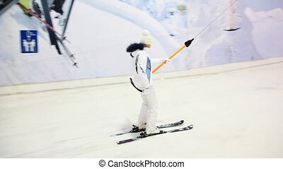 skier girl sitting on handle goes up hill in winter sport center