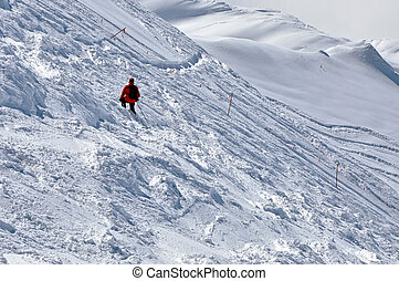 Skier going down the mountain on a slope in a sunny day