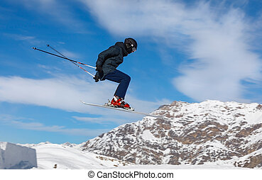 Skier jumps in the snowy mountains