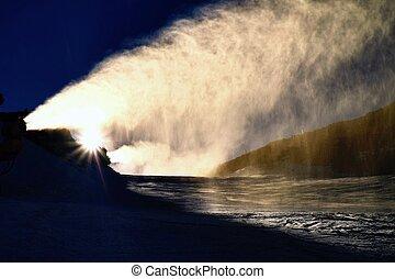 Skier near a snow cannon making powder snow. Alps ski...