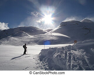 skier on a windblown snow covered piste under blue sky