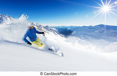 Skier on piste running downhill in beautiful Alpine...