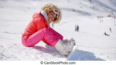 Skier putting on her snowboard - Happy young woman strapping...
