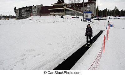 Skier rides a lift Magic Carpet