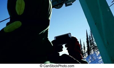 Skier rides in glasses lift chairs on sunny winter day up...