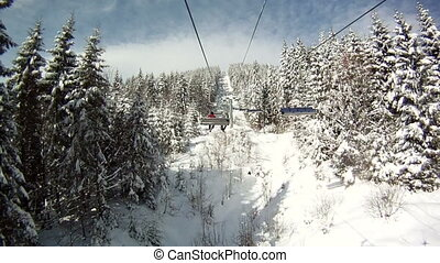 Skier rises on the ski lifts. Around Panorama and landscapes of mountains, snow-covered trees. View from the ski lift.
