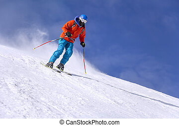 Skier skiing downhill in high mountains and sunny day