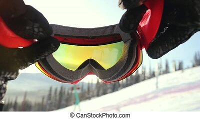 Skier wearing glasses on the background of sky with sun and mountains in slowmotion. 1920x1080