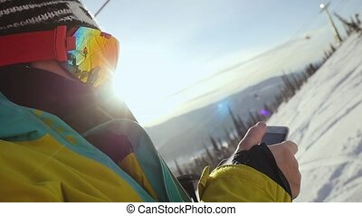 skier with mobile phone on chair lift through the sunshine...