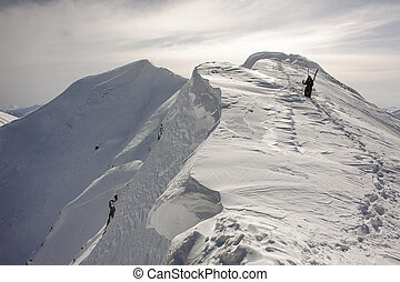 Skier with skiing equipment goes down the mountain