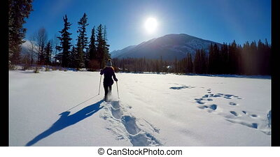 Skier woman walking on snowy landscape during winter 4k -...