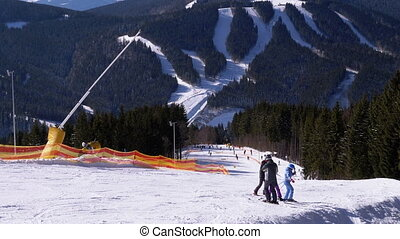 Skiers and Snowboarders Ride in Mountains on a Snowy Slope at a Ski Resort in Sunny Day