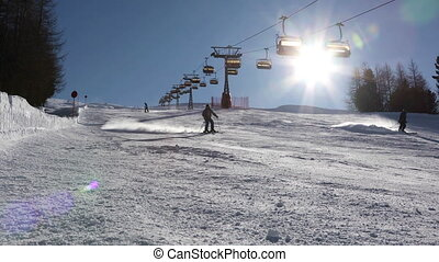 Skiers go skiing on the ski slope in the bright sun. Livigno...