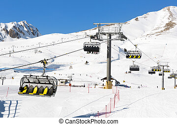 Skiers going up on the chairlift against bright blue sky- ski resort in Italy on sunny winter day