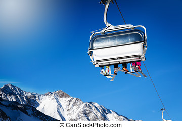 skiers in a chairlift against blue sunny sky at ski resort