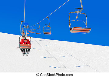 Skiers in Christmas Santa hats at skiing health resort chairlift