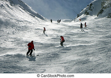 Skiers in the Alps - Skiers on Swiss Alps slopes. Snow blown...