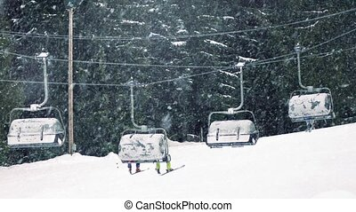 Skiers On Chairlift In Snowfall