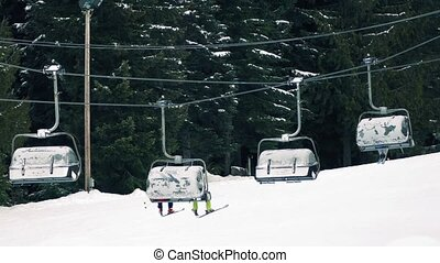 Skiers On Chairlift With Their Legs - Skiers passing by on...