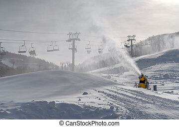 Skiers on ski lifts overlooking a snow cannon. Skiers on ski...