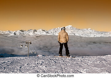 Snowboarder admiring the panorma before forsome surfing in the courchevel' ski slopes, France. unrecognizable faces.