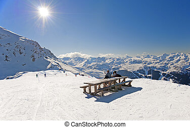 Skiers relaxing on piste - Two skiers sat at picnic table ...