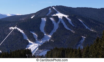Skiers Ride in Mountains on a Snowy Slope at a Ski Resort in Sunny Day