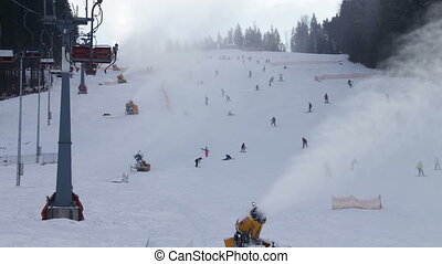 Skiers ride on the ski slopes and snow cannons. - Many...