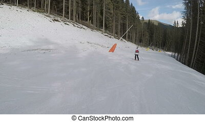 Skiers skiing down on slopes in ski resort in the...