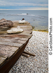 Skiff boat on stone beach by the ocean with stones on boat...