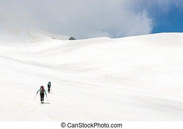Skiiers ascending mountain slope, Jalovec, Slovenia