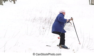 Skiing in forest - Old lady skiing in a winter forest