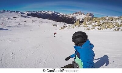 Skiing in the Alps in the winter. A man is rolling on a...