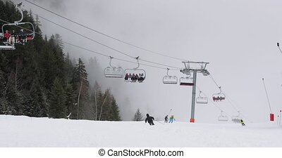Unrecognizable people using ski lift in the Alps, skiing on the slopes