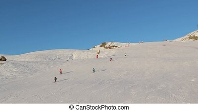 Using ski lift in the Alps, people skiing on the slopes